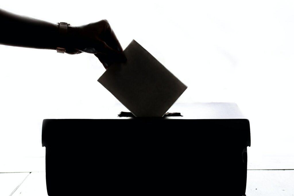 person dropping election ballot into box